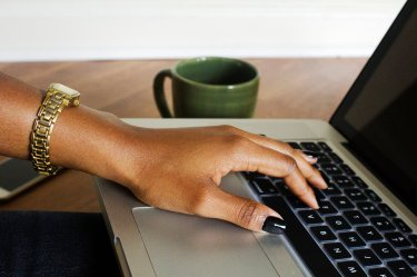 A woman's hand on a laptop