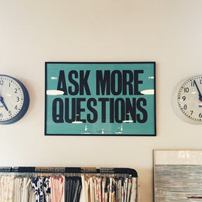 Photo of a wall with 2 clocks and a sign that reads, Ask more questions.